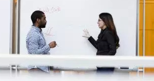 Man and woman talking at whiteboard